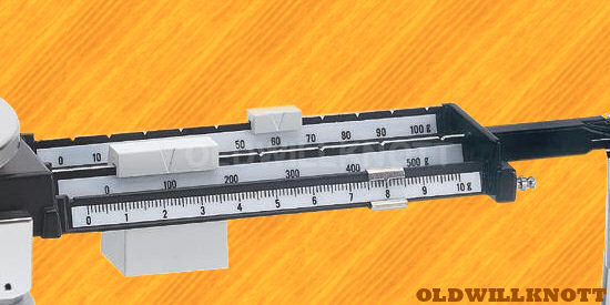Detailed image of the Triple Beam's tiered weighing beams.